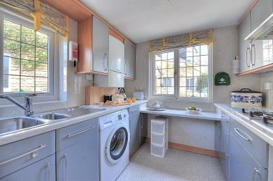 The kitchen with washing machine and sink.