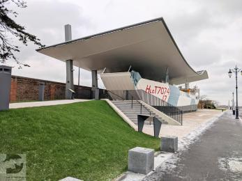 A photograph of Landing Craft Tank 7074 on display outside The D-Day Story museum. There is a ramp leading up to the entrance.