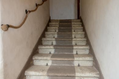 Photo of steps from landing to east first floor showing risers and rope handrail