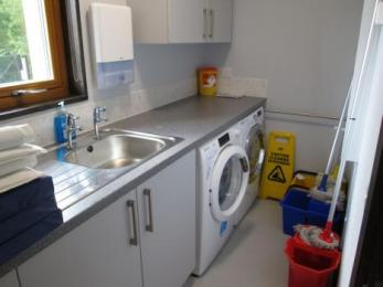 Utility room with an automatic washing machine, tumble-dryer and sink