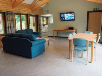 Lounge with 50 inch wall-mounted LED TV and view into kitchen area