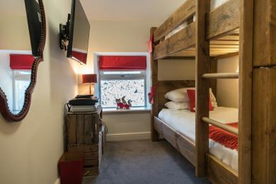 The bunk room has single bed sized beds and under-bed storage for clothes.
