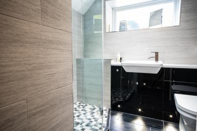 The family bathroom has a large walk in shower with a basin set in a vanity unit and a toilet