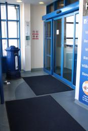 Foyer with dark mats and inner automatic doors