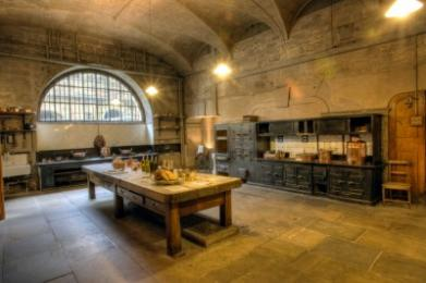 The Old Kitchen. There is a central wooden table and a large kitchen range.