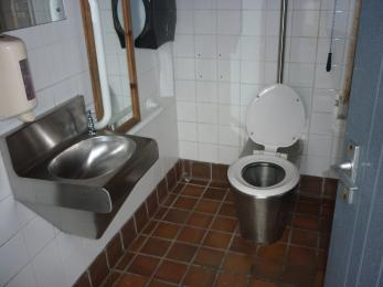 A white tiled bathroom showing rails near the toilet and a wall hung sink.