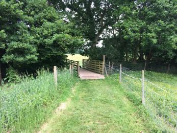 The grassy pathway from the car park to the glamping field with bridge and 2 steps (10cm and 15cm up)