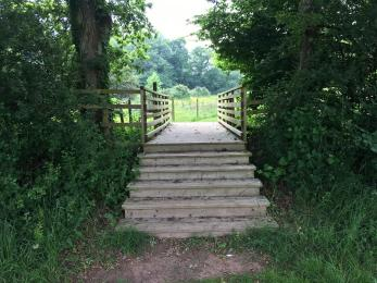 Steps down from the footbridge into the glamping field (15cm drop on each step, 40cm depth)