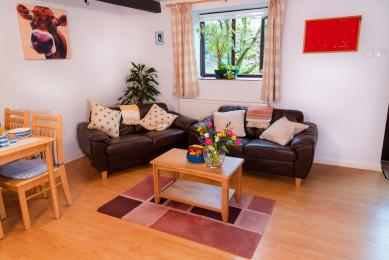 Blackberry Cottage's two 2-seater 'leather-effect' sofas, with a picture of a cow on the wall.