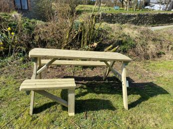Table and chairs in Polrunny Farm's breakfast garden, with space for a wheelchair-user to sit at the garden table.