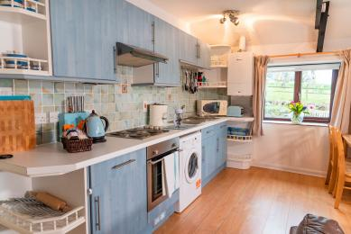 The kitchen at Polrunny Farm's Elderberry Cottage, with a mix of low and high-level units.