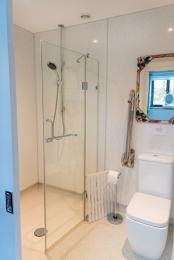 'Wet room'-style bathroom, with remote controlled shower, toilet with fold-down hand-rails and accessible sink