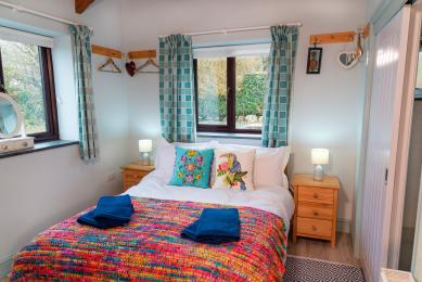 Sloe Cottage is light and airy. Image shows the double-aspect windows in the bedroom.