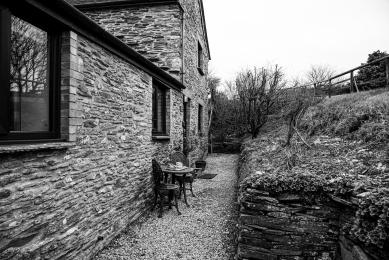 Black and white image of the gravel path up to Polrunny Farm's Blackberry Cottage, with table and chairs outside the front door