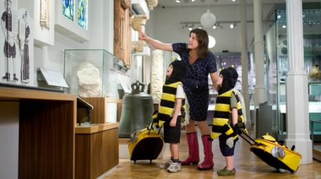 A photograph of two children in bee costumes with Beastie bags looking around the museum.