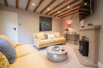 Family room leading from the sitting room with two large sofas small coffee table and tv located on the chimney breast