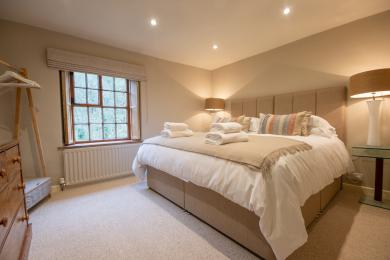 Bedroom 1 with a super king or twin beds, chest of drawers and garment hanging rail.