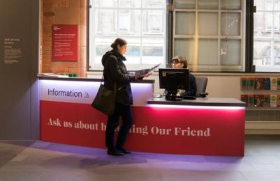 Scottish National Portrait Gallery - information desk, front view with member of gallery staff and visitor