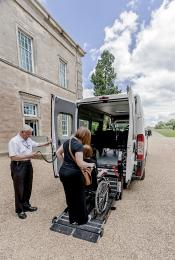 The minibus shuttle with ramp in operation to assist a wheelchair user and their helper