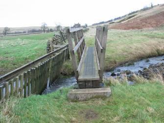 Narrow Footbridge with rails Crossing Stream