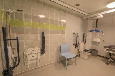 Accessible bathroom with accessible shower with fixed and portable shower seats