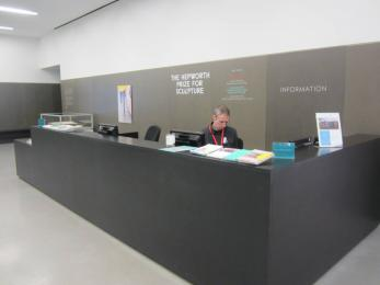 The Welcome Desk is a short distance from the main entrance and is medium height. Part of the desk is lower level for easy acces