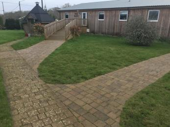 lawns and paths leading to ramp to main entrance