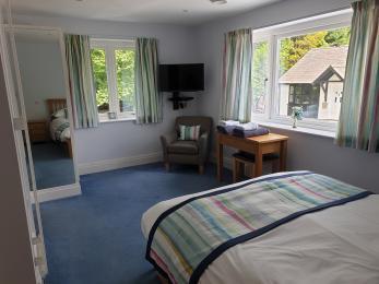 Downstairs king sized bedroom showing wall  mounted TV/DVD, windows to river and courtyard and access between bed and radiator