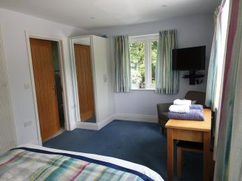 Downstairs bedroom showing river window, door to en-suite wet room, TV/BluRay DVD