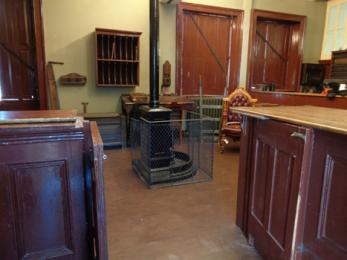 View of Victorian booking office showing partition open and fireplace in centre of room