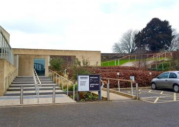A photograph of the two blue-badge holder's parking spaces, the stairs and the ramp to the Garden Entrance