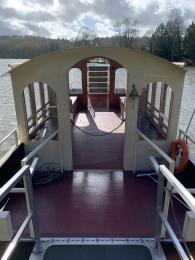 The ferry interior. There is a metal ramp lowered from the ferry to the jetty.