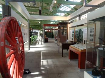 View of some museum displays showing large red wheel in foreground