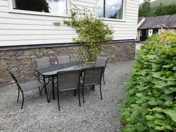 secluded semi-enclosed dining area, with table and six chairs. Fell views
