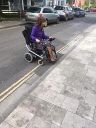 Photo shows a wheelchair user coming up the ramp from the road to the pavement outside The Novium Museum.