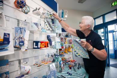 A volunteer puts souvenirs on display in the shop