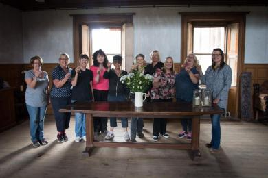 Photo of some hard-working Bannockburn House volunteers beside the table in the main hall used as reception and information desk