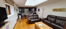 Brew House Living space with kitchen, dining and lounge areas having reclining leather sofas and great art work