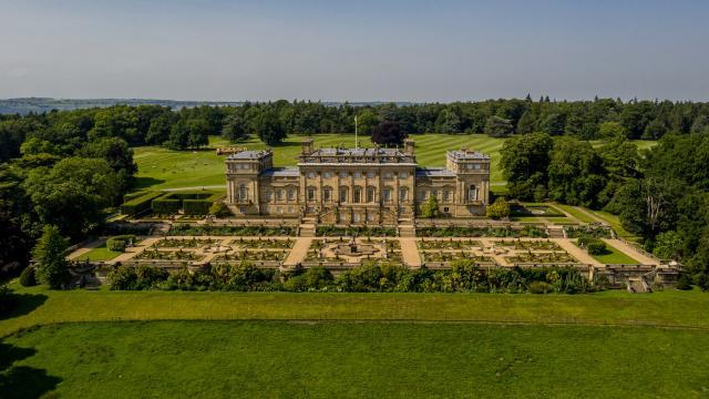 A large Palladian-style stone stately home with a formal terrace garden set in green rural landscape.