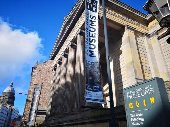 Picture of the neoclassical  Playfair building on Nicolson Street with a banner with the museum logo and a sign for the museum.