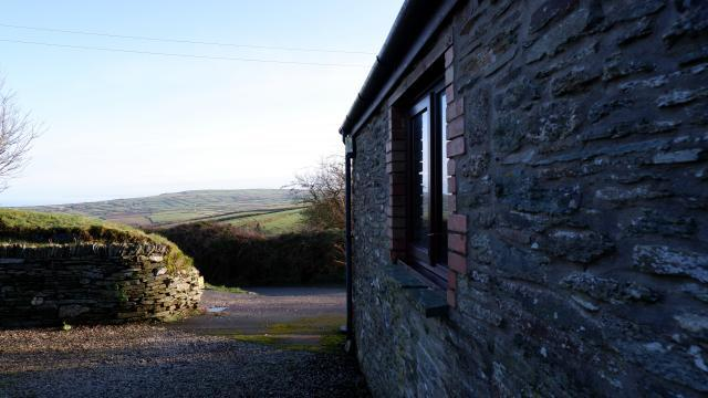 The stone wall of Elderberry Cottage at Polrunny Farm, with expansive views of the countryside as it slopes down to the sea.