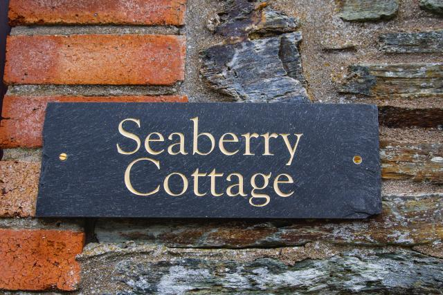 Slate sign with 'Seaberry Cottage written in ivory-coloured writing.