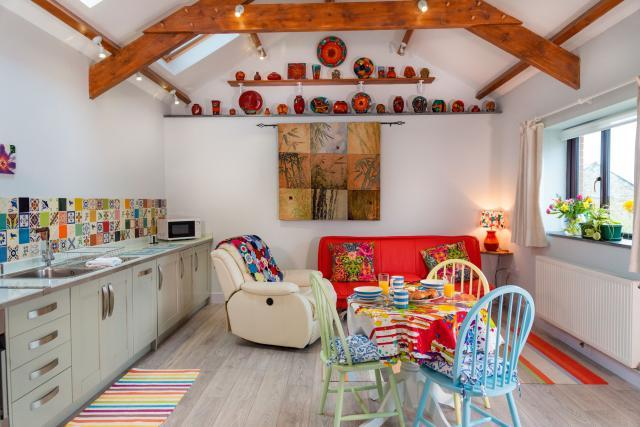 The  kitchen lounge diner in Sloe Cottage at Polrunny Farm, with beautiful tapestries and pottery in view.