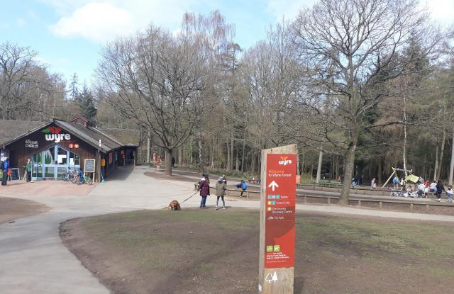 Image of outside of cafe building, playarea and tarmac paths leading downhill to start of walking trails.